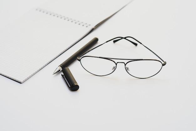 Leeres tagebuch, stift und brille auf weißem hintergrund