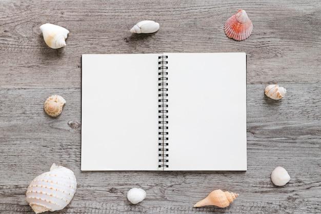 Leeres tagebuch und seeshell vereinbarten auf tabelle