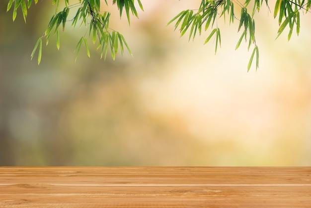 Leeres tischholz und bambus verlassen auf bokeh-naturhintergrund.