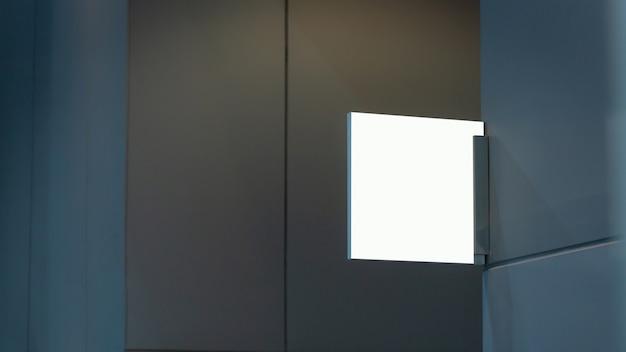 Leeres transparentes zeichenschildentwurfs-entwurfsmodell an der wand nahe büroeinganginnenraum. beschilderungstür türnummer vorlage.