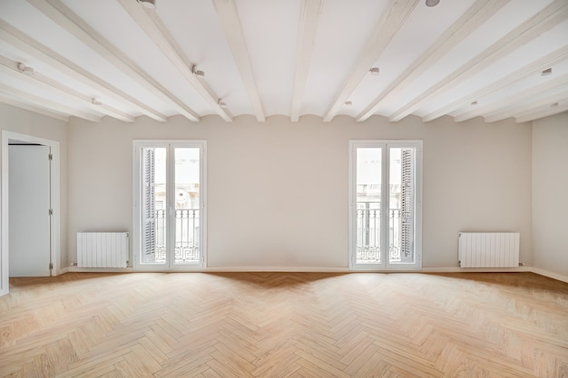 Leeres und sauberes zimmer in einer renovierten wohnung mit holzboden und zwei balkonen, hellem immobilieninterieur