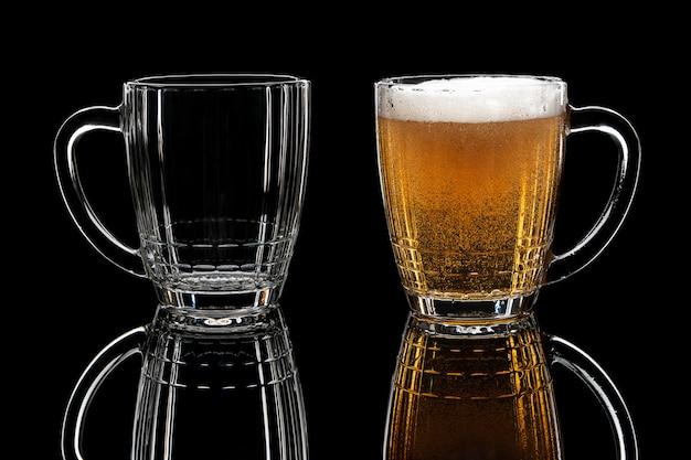 Leeres und volles glas bier auf schwarzem hintergrund