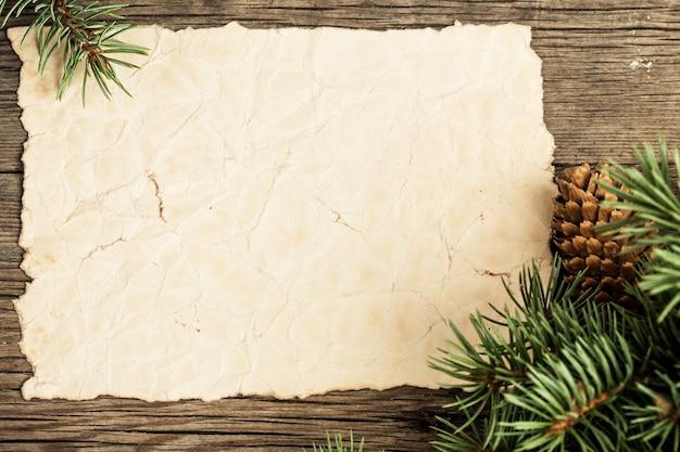 Leeres vintage-papier gerahmter zweig des weihnachtsbaums auf holz