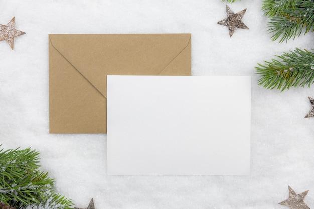 Leeres weihnachtsgrußkartenmodell mit handwerksumschlag und weihnachtsbaumzweigen und dekoration auf schneehintergrund
