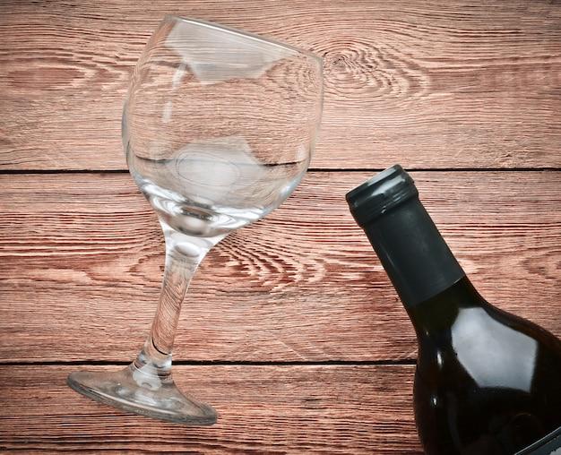 Leeres weinglas und eine flasche wein auf einem holztisch. vorbereitung auf den urlaub. draufsicht.