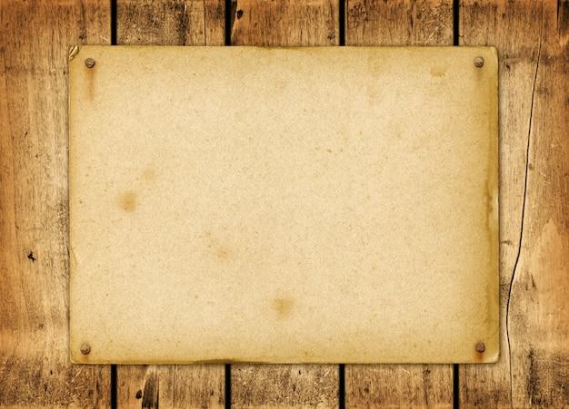 Leeres weinlesepapier genagelt auf einem hölzernen brett