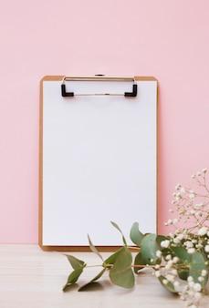 Leeres weißbuch auf klemmbrett mit blättern und babyatem blüht auf hölzernem schreibtisch gegen rosa hintergrund