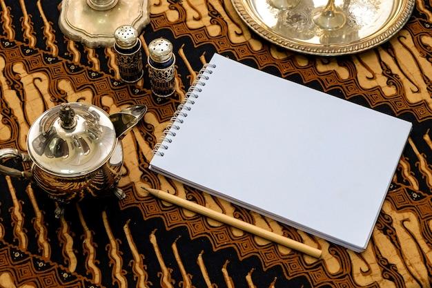 Leeres weißbuch-notizbuch im batik-gewebe-hintergrund mit silbernen stoffen