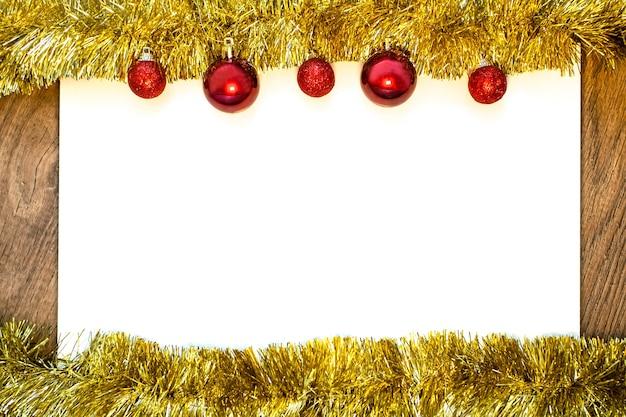 Leeres weißes blatt papier mit goldenem lametta und roten weihnachtskugeln. flacher laienstil. copyspace.