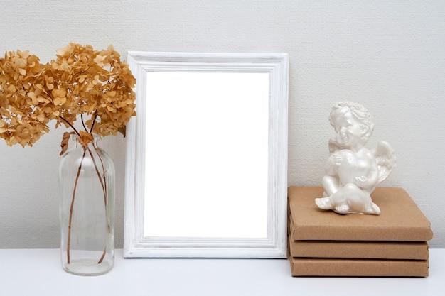 Leeres weißes drahtmodell mit glasvase und büchern auf dem tisch. holzrahmen für ihren text.