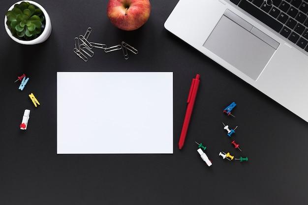 Leeres weißes kartenpapier mit stift; apfel; bunte büromaterialien und laptop auf schwarzem hintergrund