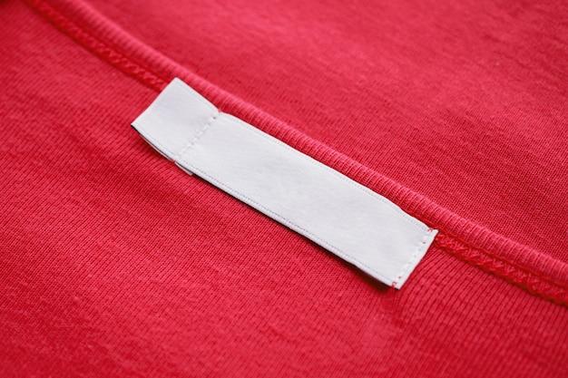 Leeres weißes kleidungsetikett auf dem neuen roten hemd