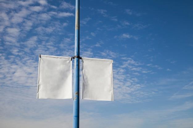 Leeres weißes laternenpfahl-fahnenplakat gegen blauen himmel
