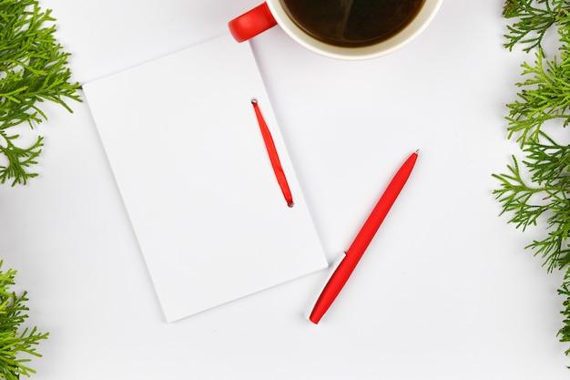 Leeres weißes notizbuch und roter stift auf weihnachtsweißraum. weihnachtstannenzweige, zapfen, geschenke. brief an den weihnachtsmann, verspotten. leeres weißes notizbuch und roter stift auf weiß.