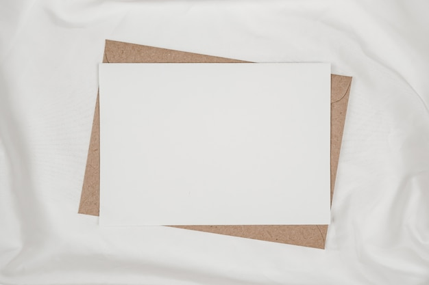 Leeres weißes papier auf braunem papierumschlag auf weißem stoff