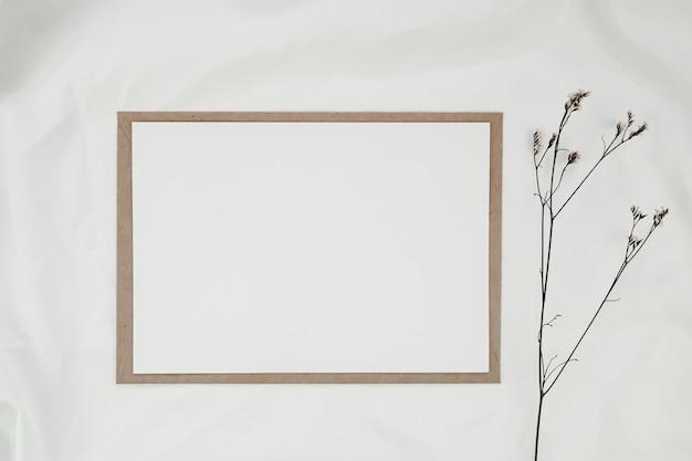 Leeres weißes papier auf braunem papierumschlag mit limonium-trockenblume auf weißem tuch. horizontale leere grußkarte. draufsicht des handwerksumschlags auf weißem hintergrund.
