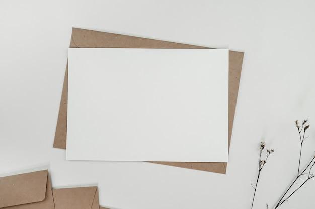 Leeres weißes papier auf braunem papierumschlag mit limonium-trockenblume. horizontale leere grußkarte. draufsicht des handwerksumschlags auf weißem hintergrund.