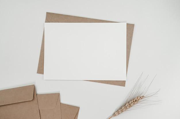 Leeres weißes papier auf braunem papierumschlag mit trockener blume der gerste. horizontale leere grußkarte. draufsicht des handwerksumschlags auf weißem hintergrund.