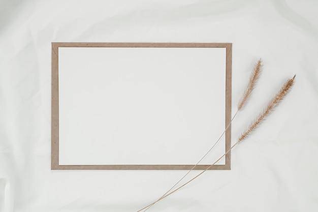 Leeres weißes papier auf braunem papierumschlag mit trockener blume des borstenfuchsschwanzes auf weißem tuch. horizontale leere grußkarte. draufsicht des handwerksumschlags auf weißem hintergrund.