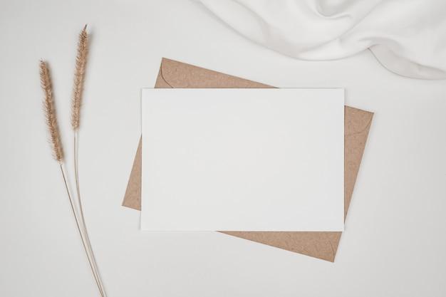 Leeres weißes papier auf braunem papierumschlag mit trockener blume des borstenfuchsschwanzes auf weißem tuch