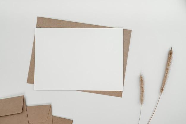 Leeres weißes papier auf braunem papierumschlag mit trockener blume des borstenfuchsschwanzes. horizontale leere grußkarte. draufsicht des handwerksumschlags auf weißem hintergrund.