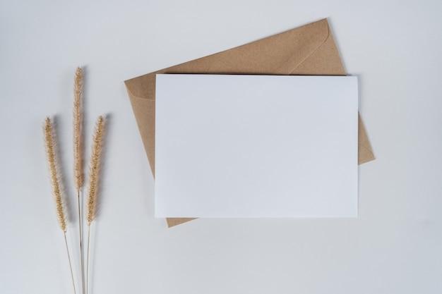 Leeres weißes papier auf braunem papierumschlag mit trockener blume des borstigen fuchsschwanzes. draufsicht des bastelpapierumschlags auf weißem hintergrund.