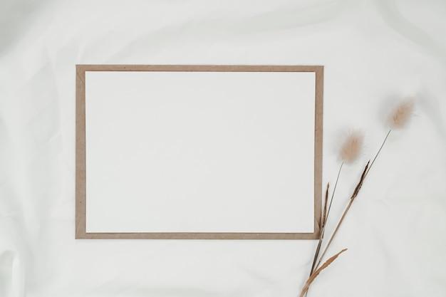 Leeres weißes papier auf braunem papierumschlag mit trockener blume des kaninchenschwanzes auf weißem tuch. horizontale leere grußkarte. draufsicht des handwerksumschlags auf weißem hintergrund