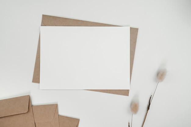 Leeres weißes papier auf braunem papierumschlag mit trockener blume des kaninchenschwanzes. horizontale leere grußkarte. draufsicht des handwerksumschlags auf weißem hintergrund.