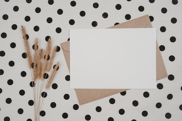 Leeres weißes papier auf braunem papierumschlag mit trockener blume mit borstenfuchsschwanz und kartonschachtel auf weißem stoff mit schwarzen punkten