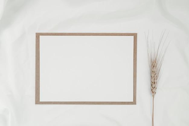 Leeres weißes papier auf braunem papierumschlag mit trockener gerstenblume auf weißem tuch. horizontale leere grußkarte. draufsicht des handwerksumschlags auf weißem hintergrund.