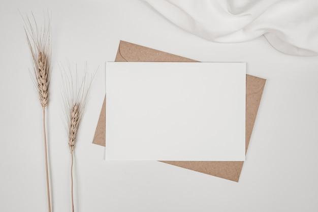Leeres weißes papier auf braunem papierumschlag mit trockener gerstenblume auf weißem tuch