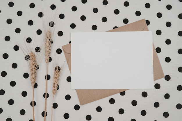 Leeres weißes papier auf braunem papierumschlag mit trockener gerstenblume und kartonschachtel auf weißem stoff mit schwarzen punkten