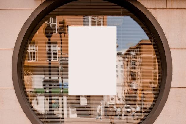 Leeres weißes papier auf dem kreisförmigen glasfenster