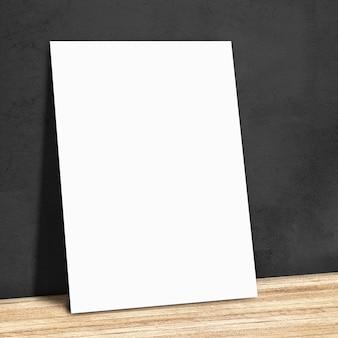 Leeres weißes papier auf der schwarzen wand und dem holzboden, mock-up für ihren inhalt