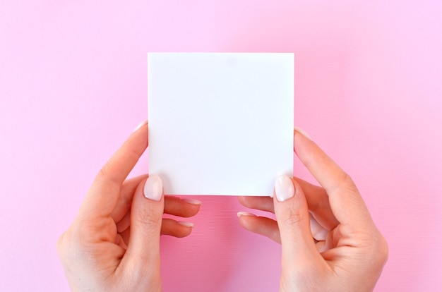 Leeres weißes papier in den weiblichen händen auf einem rosa hintergrund, als modell für ihr design. minimale komposition im flat-lay-stil.