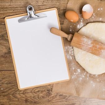 Leeres weißes papier in der zwischenablage; flacher teig und eierschalen auf pergamentpapier über dem holztisch