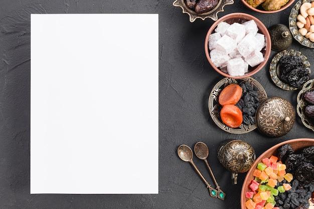 Leeres weißes papier mit arabischen süßigkeiten; getrocknete früchte; nüsse für ramadan auf schwarzem hintergrund