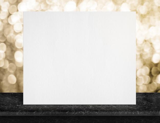 Leeres weißes papierplakat auf schwarzer marmortischplatte und funkelndes goldenes bokehlicht