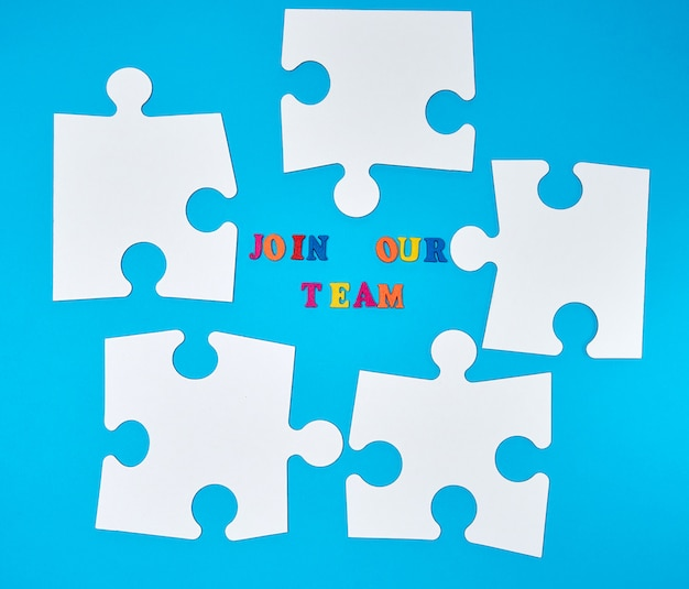 Leeres weißes papierpuzzlespiel auf einem blauen hintergrund, die aufschrift verbinden unser team