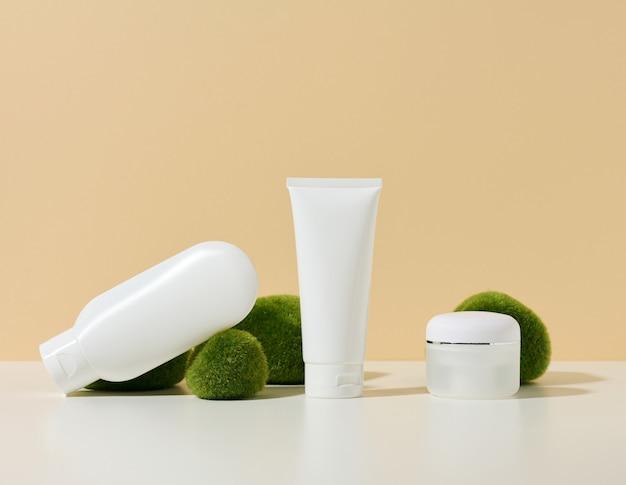 Leeres weißes plastikrohr, glas mit einem brecher in der nähe von steinen mit moos auf beigem hintergrund. kosmetische produkte zum branding von gel, creme, lotion, shampoo. attrappe, lehrmodell, simulation