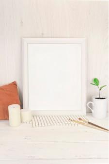 Leeres weißes rahmenmodell mit kleinem zweig saftiger zamioculcas in einem vasenbecher der weinlese
