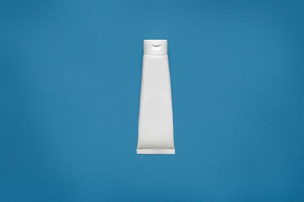 Leeres weißes röhrenentwurfsmodell lokalisiert auf blauem, beschneidungspfad. klare cremeverpackung, modell. lotion hautpflege leeren verpackungsbehälter. hautpflege, kosmetisches konzept. gel, tube, flakon.