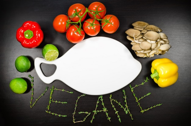 Leeres weißes schneidebrett gestaltete das gemüse und den text vegetarier