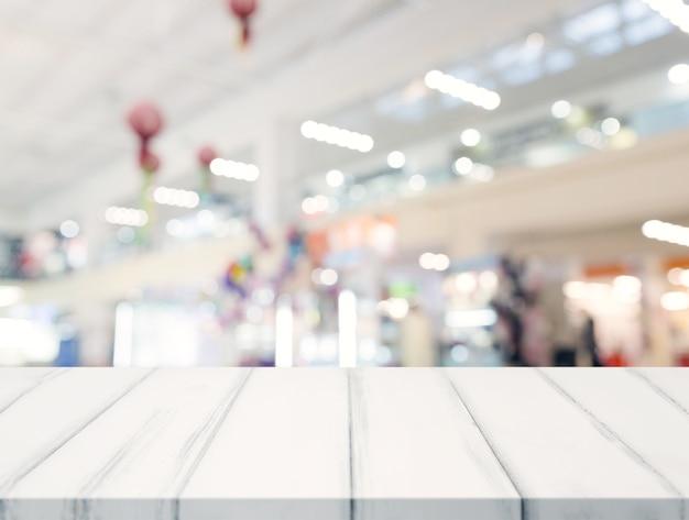 Leeres weißes tischplatte- und unschärfeeinkaufszentrum im hintergrund