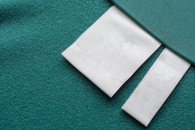 Leeres weißes wäschepflege-kleidungsetikett auf grünem stoffbeschaffenheitshintergrund