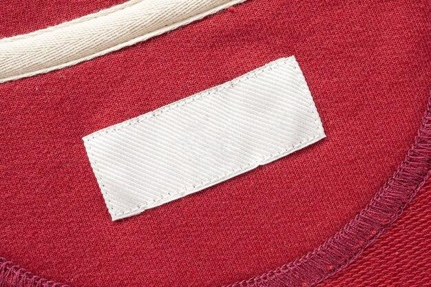 Leeres weißes wäschepflege-kleidungsetikett auf rotem stoffbeschaffenheitshintergrund