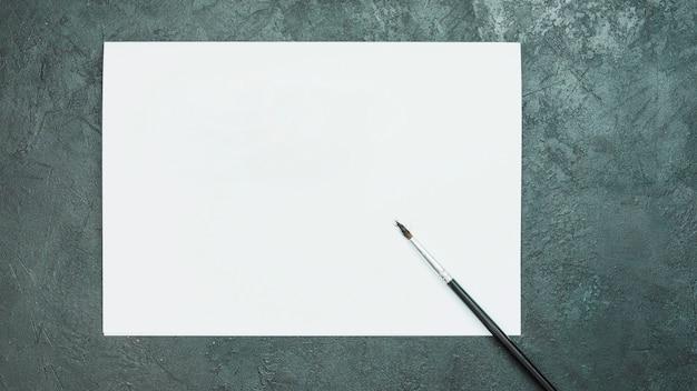 Leeres weißes zeichenpapier mit pinsel auf dem schwarzen schieferfelsen gemasert