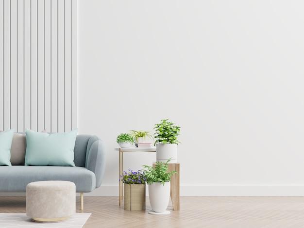Leeres wohnzimmer mit blauem sofa, pflanzen und tisch auf leerer weißer wand