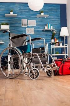 Leeres wohnzimmer mit niemandem darin, der einen medizinischen rollstuhl neben der roten tasche für die krankenhausrehabilitation hat