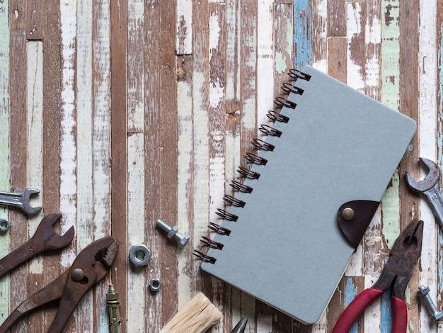 Leerraumabdeckung-anmerkungsbuch und alte rostige handliche arbeitsgeräte auf gruge hölzernem hintergrund.